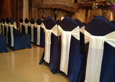 The Notley Tythe Barn - Using their Navy Covers with our Cream Satin Sashes tied in the drop knot style